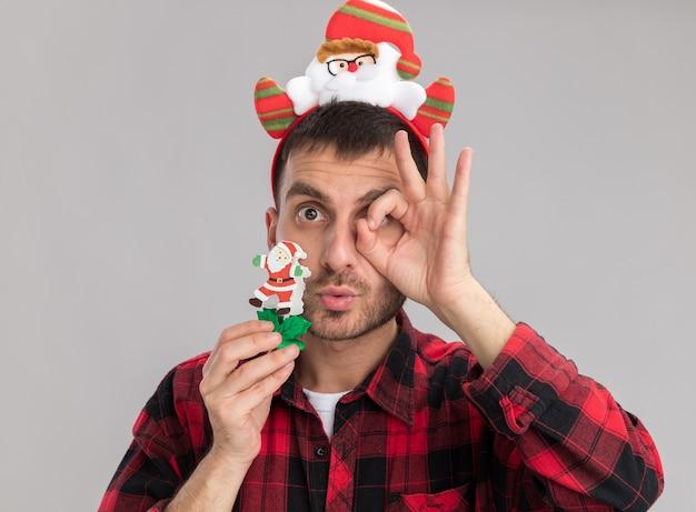 Впечатленный молодой кавказский человек в головной повязке санта-клауса, держащий рождественскую игрушку снеговика, смотрящий в камеру, делает жест взгляда изолирован на белом фоне