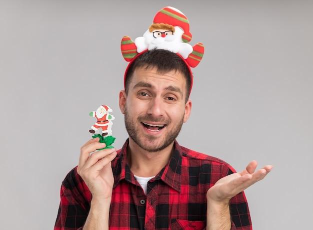 白い背景で隔離の空の手を示すカメラを見て雪だるまのクリスマスのおもちゃを保持しているサンタクロースのヘッドバンドを身に着けている印象的な若い白人男性