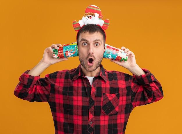 Впечатленный молодой кавказский мужчина в повязке на голову санта-клауса смотрит в камеру, держа пластиковые рождественские чашки рядом с ушами, изолированными на оранжевом фоне