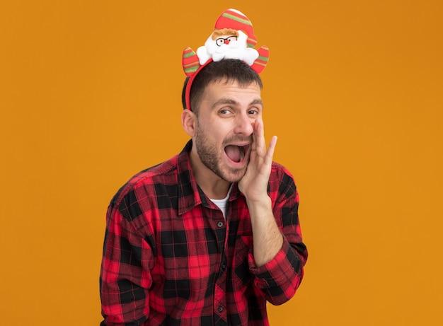 Impressionato giovane uomo caucasico indossando la fascia di babbo natale guardando la telecamera tenendo la mano vicino alla bocca sussurrando isolato su sfondo arancione