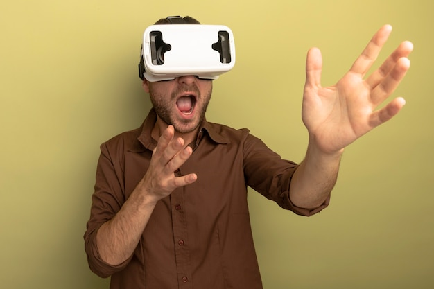 Impressed young caucasian man wearing vr headset looking at side stretching out hands isolated on olive green background