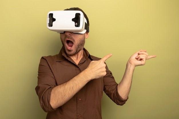 Impressed young caucasian man wearing vr headset pointing at side isolated on olive green background