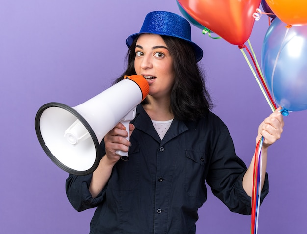Impressed young caucasian party girl wearing party hat holding bunch of balloons  talking by speaker isolated on purple wall