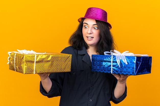 오렌지 벽에 고립 된 하나를보고 선물 패키지를 들고 파티 모자를 쓰고 감동 젊은 백인 파티 소녀