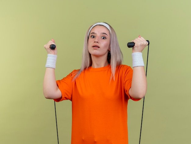 Впечатленная молодая кавказская спортивная девушка с подтяжками, носящая повязку на голову и браслеты, держит скакалку