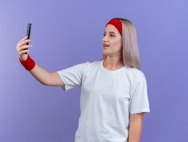 Впечатленная молодая кавказская спортивная девушка с подтяжками в головной повязке