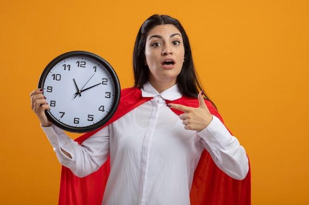 Впечатленная молодая кавказская девушка супергероя, держащая и указывающая на часы, смотрящая в камеру, изолированную на оранжевом фоне