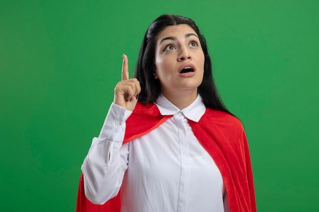 Impressionato giovane ragazza caucasica del supereroe che mette il dito indice con la bocca aperta che osserva in su isolato sulla parete verde con lo spazio della copia