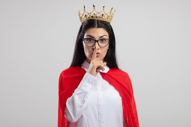 Впечатленная молодая кавказская девушка супергероя в очках и короне, смотрящая в камеру, делает жест молчания на белом фоне с копией пространства