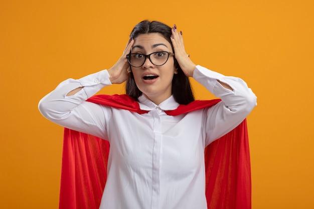 オレンジ色の背景で隔離の頭に手を置いてカメラを見て眼鏡をかけている感動の若い白人のスーパーヒーローの女の子