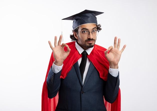 Впечатленный молодой кавказский супергерой в оптических очках, одетый в костюм с красным плащом и выпускной кепкой, жестикулирует знак рукой двумя руками