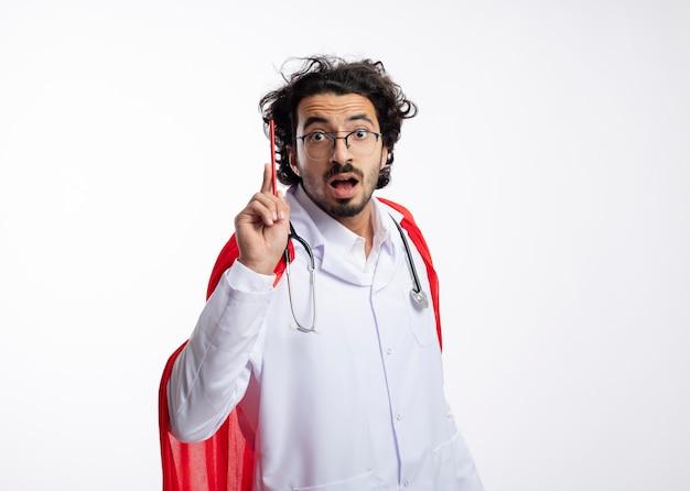 Impressionato giovane supereroe caucasico uomo in occhiali ottici che indossa l'uniforme del medico con mantello rosso e con lo stetoscopio intorno al collo tiene la matita