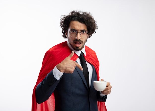 Impressionato il giovane supereroe caucasico con occhiali ottici che indossa un abito con mantello rosso tiene e punta alla tazza