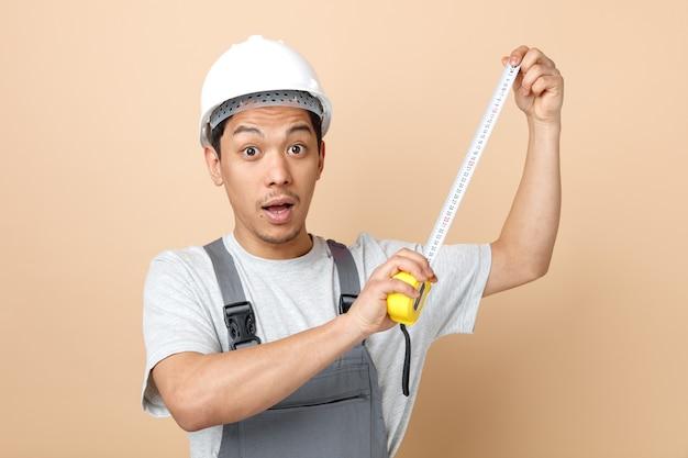 안전 헬멧 및 테이프 측정기를 들고 유니폼을 입고 감동 된 젊은 건설 노동자