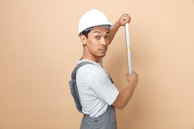 安全ヘルメットを着用し、レベル定規を保持している縦断ビューで制服を着て感銘を受けた若い建設労働者