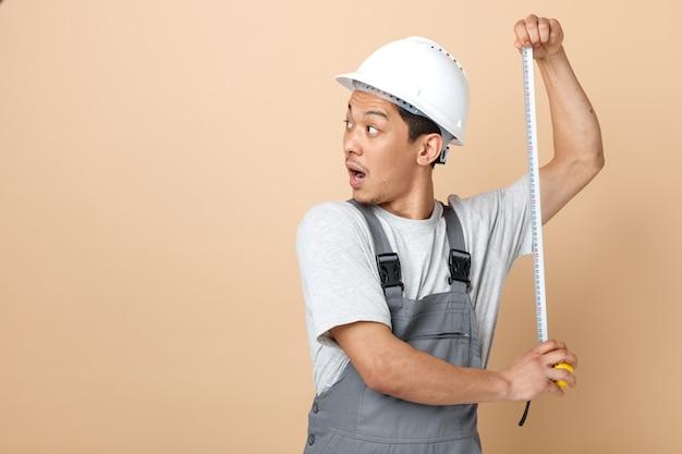 Impressionato giovane operaio edile che indossa il casco di sicurezza e metro a nastro di tenuta uniforme guardando a lato