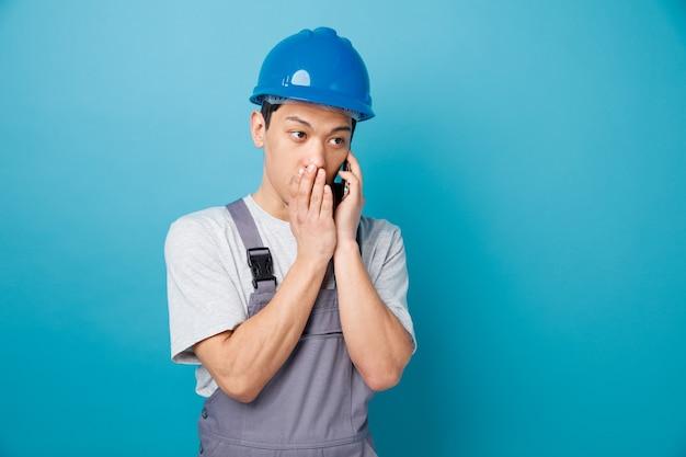 Impressionato giovane operaio edile che indossa il casco di sicurezza e sussurra uniforme sul telefono guardando a lato