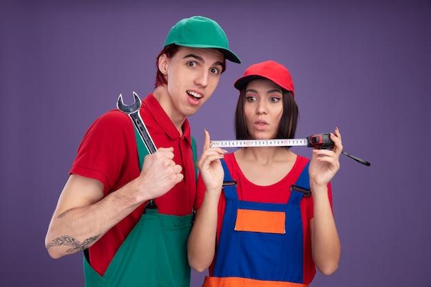 Impressionato giovane coppia in uniforme da operaio edile e berretto ragazza che tiene e guarda il ragazzo del metro a nastro che tiene la chiave guardando la telecamera isolata sul muro viola