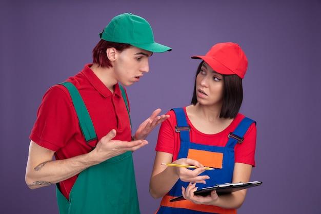 Impressionato giovane coppia in uniforme da operaio edile e berretto ragazza che tiene matita e appunti guardando il ragazzo e lui che mostra le mani vuote guardando gli appunti isolati sul muro viola