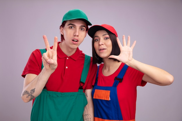 Impressed young couple in construction worker uniform and cap looking at camera guy showing two with hand girl showing five with hand isolated on white wall