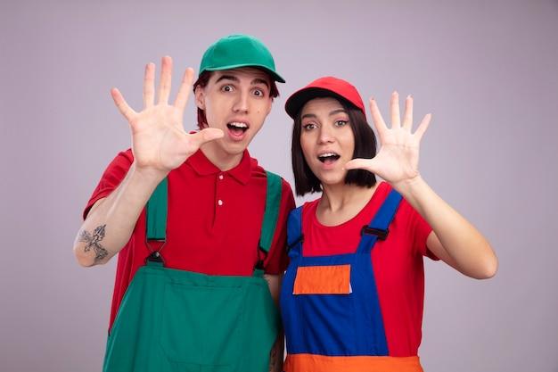 Impressionato giovane coppia in uniforme da operaio edile e berretto guardando la telecamera che mostra cinque con la mano isolata sul muro bianco