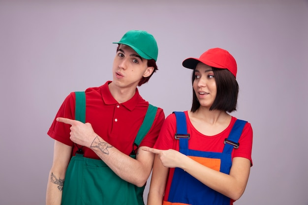 Impressed young couple in construction worker uniform and cap pointing at side guy looking at camera girl looking at side isolated on white wall