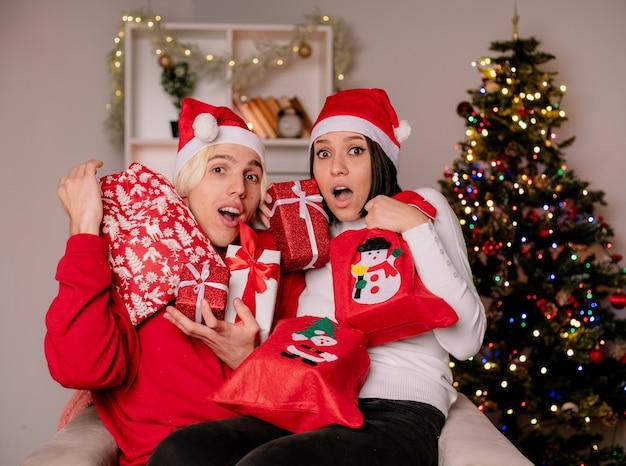 Impressionato giovane coppia a casa nel periodo natalizio indossando il cappello di babbo natale seduto sulla poltrona che tiene pacchetti e sacchi regalo di natale guardando la fotocamera in soggiorno