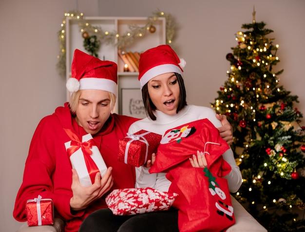 Impressionato giovane coppia a casa nel periodo natalizio indossando il cappello di babbo natale seduto sulla poltrona tenendo e guardando i pacchetti e i sacchi regalo di natale in soggiorno