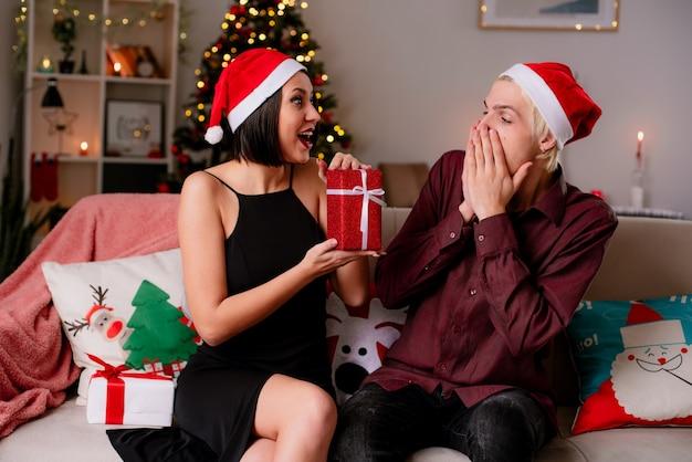Impressionato giovane coppia a casa nel periodo natalizio indossando il cappello della santa seduto sul divano in soggiorno ragazza che dà il pacchetto regalo al suo ragazzo guardandolo lui guardando il regalo tenendo le mani sulla bocca