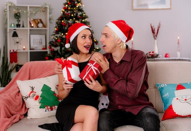 Impressionato giovane coppia a casa nel periodo natalizio indossando il cappello della santa seduto sul divano in soggiorno ragazza che tiene i pacchetti regalo di natale ragazzo che la tiene per le spalle