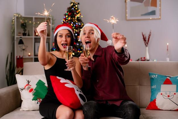 Impressionato giovane coppia a casa nel periodo natalizio indossando il cappello della santa seduto sul divano nel soggiorno con in mano un bicchiere di champagne e una scintilla natalizia con cuscino natalizio sulle gambe