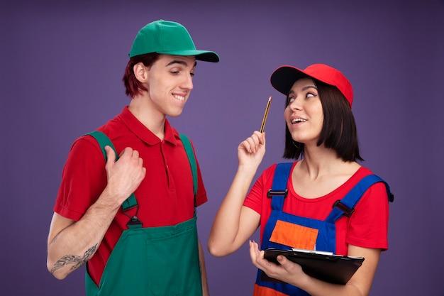 Впечатленная молодая пара в униформе строителя и кепке девушка держит карандаш и буфер обмена, глядя на парня, указывая вверх с карандашом, парень кусает губу, глядя в буфер обмена, касаясь его униформы