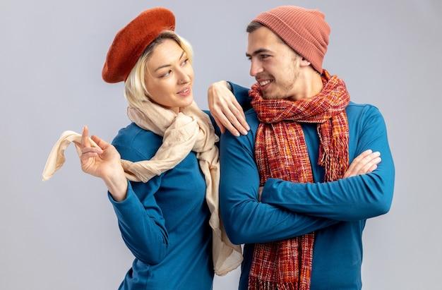 Impressionato giovane coppia il giorno di san valentino indossando un cappello con sciarpa guardando l'altro isolato su sfondo bianco