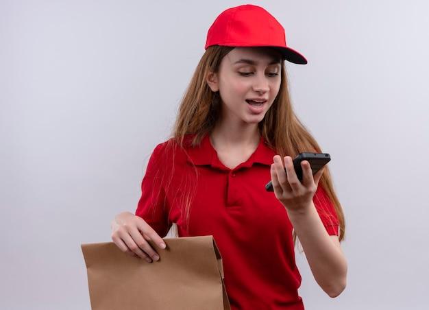 Впечатленная молодая доставщица в красной форме, держащая и смотрящая на мобильный телефон на изолированном белом пространстве