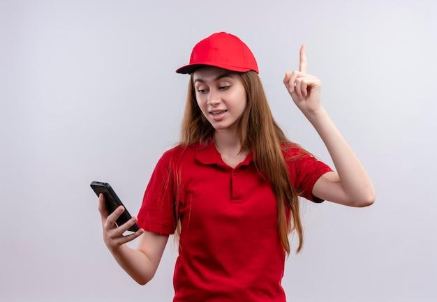 Впечатленная молодая доставщица в красной форме, держащая и смотрящая на мобильный телефон с поднятым пальцем на изолированном белом пространстве
