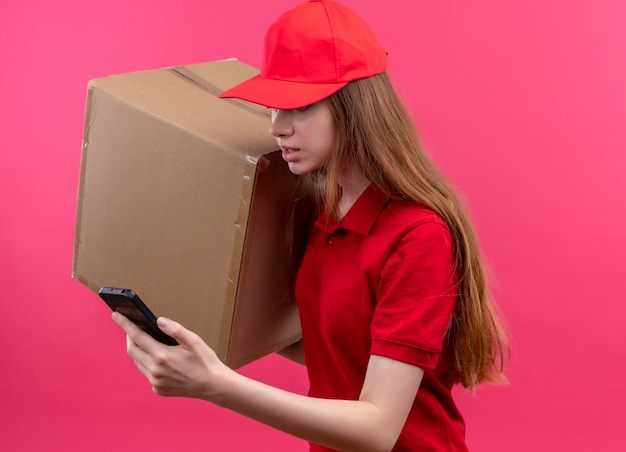 Впечатленная молодая доставщица в красной форме, держащая коробку и мобильный телефон, смотрящую на мобильный телефон, стоящий в профиле на изолированном розовом пространстве