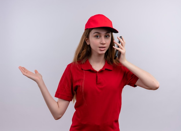 빨간색 유니폼 휴대 전화를 들고 고립 된 공백에 빈 손을 보여주는 감동 된 젊은 배달 소녀