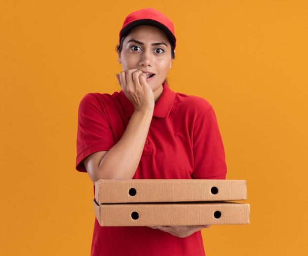 オレンジ色の壁に隔離された爪を噛むピザの箱を保持している制服と帽子を身に着けている感動の若い配達の女の子