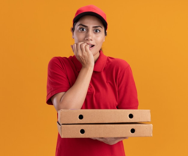 Impressed young delivery girl wearing uniform and cap holding pizza boxes bites nails isolated on orange wall