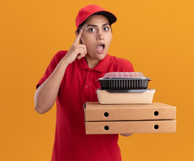 Impressionato giovane ragazza di consegna che indossa l'uniforme e il cappuccio che tiene le scatole per pizza con contenitori per alimenti che mettono il dito sul tempio isolato sulla parete arancione