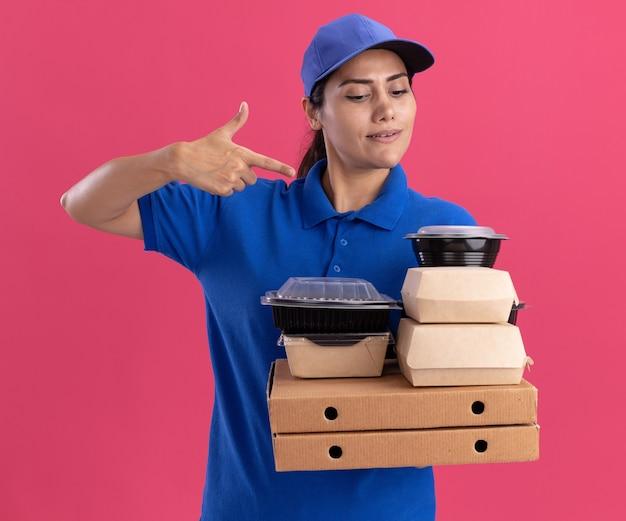 분홍색 벽에 고립 된 피자 상자에 음식 용기에 모자를 들고와 포인트 유니폼을 입고 감동 젊은 배달 소녀