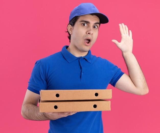 Impressionato giovane fattorino in uniforme blu e cappuccio che tiene i pacchetti di pizza guardando davanti mostrando cinque con la mano isolata sul muro rosa