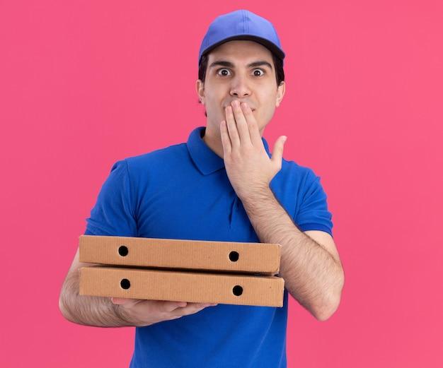 Impressionato giovane fattorino in uniforme blu e cappuccio che tiene i pacchetti di pizza mettendo la mano sulla bocca guardando la parte anteriore isolata sul muro rosa
