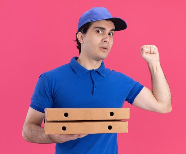 파란색 유니폼을 입고 피자 패키지를 들고 있는 모자를 쓴 젊은 배달원은 분홍색 벽에 격리된 노크 제스처를 하며 정면을 바라보고 있습니다.