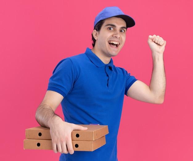 파란색 유니폼을 입은 젊은 배달원과 분홍색 벽에 격리된 앞을 바라보는 노크 제스처를 하는 피자 패키지를 들고 프로필 보기에 서 있는 모자