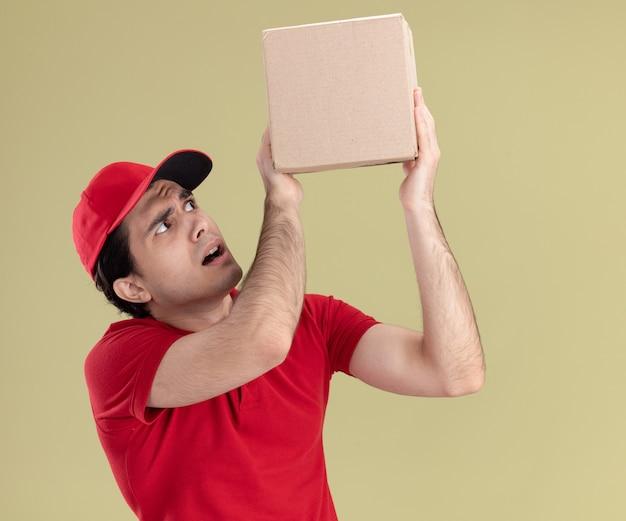 빨간 제복을 입은 젊은 배달원과 모자를 들고 올리브 녹색 벽에 격리된 카드박스를 보고 있는 모습
