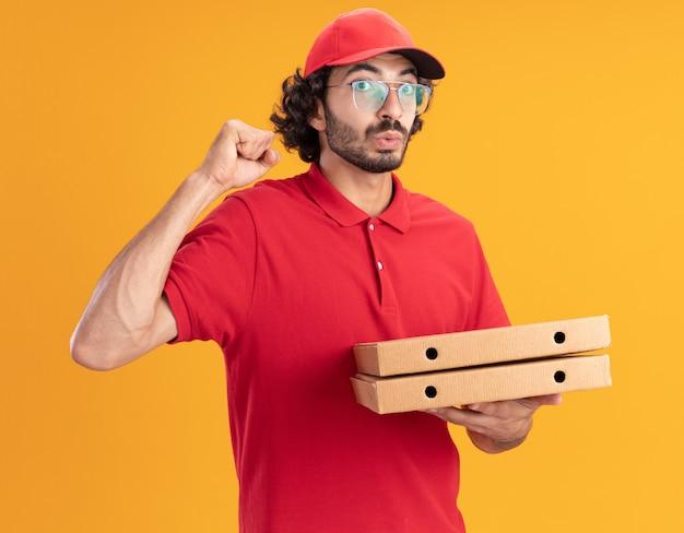 주황색 벽에 격리된 강한 제스처를 하고 있는 정면을 바라보며 피자 패키지를 들고 안경을 쓴 모자를 쓴 빨간 유니폼을 입은 젊은 배달원