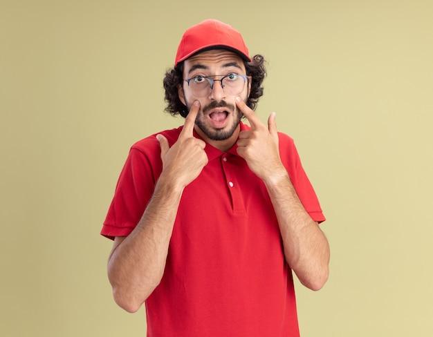 올리브 녹색 벽에 격리된 뺨에 손가락을 대고 앞을 가리키는 안경을 쓰고 빨간 제복을 입은 젊은 배달원