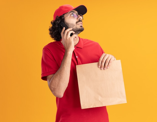 Impressionato giovane fattorino in uniforme rossa e berretto con gli occhiali che tiene in mano un pacchetto di carta che parla al telefono guardando il lato isolato sul muro arancione