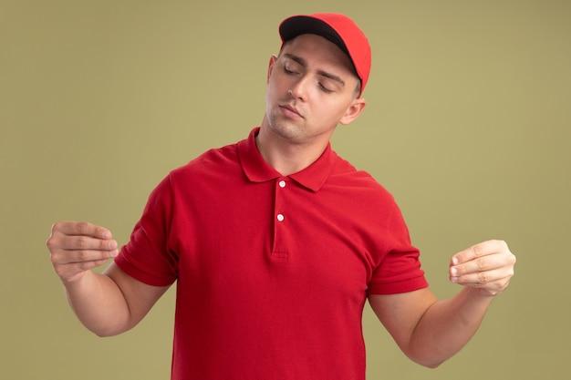 オリーブグリーンの壁に隔離された何かを保持しているふりをして制服とキャップを身に着けている感動の若い配達人